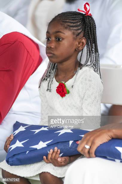 Ah'Leesya Johnson holds a folded US flag given to her during the burial service for her father US Army Sgt La David Johnson at the Memorial Gardens...