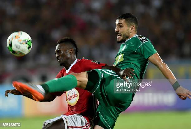 Ahly Tripoli's forward Mohamed Abrahim vies with Etoile du Sahel Alkhaly Bangoura during the African Champions league quarterfinal football match in...