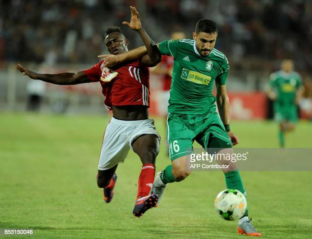Ahly Tripoli's forward Mohamed Abrahim vies with Etoile du Sahel's Alkhaly Bangoura during the African Champions league quarterfinal football match...