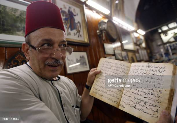 Ahmad alLahham a Syrian storyteller reads from his storybook in a Damascus coffeehouse on June 19 2017 / AFP PHOTO / LOUAI BESHARA