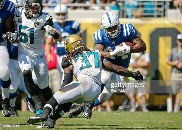 Ahmad Bradshaw of the Indianapolis Colts carries as Johnathan Cyprien of the Jacksonville Jaguars defends during the game at EverBank Field on...