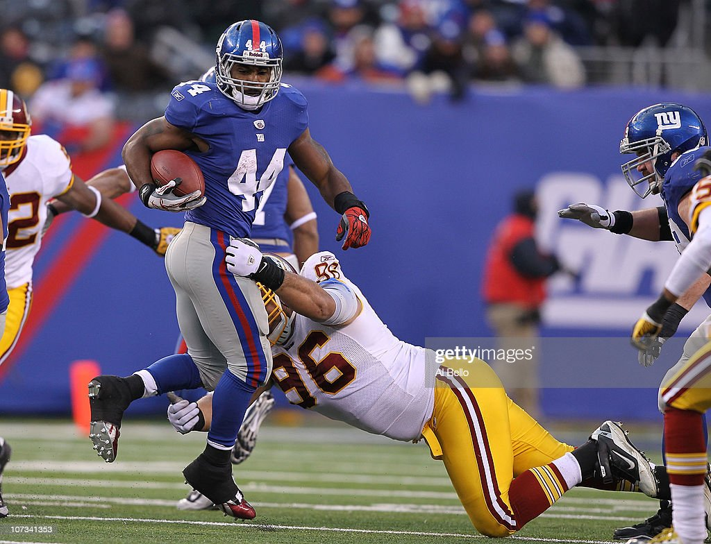 Ahmad Bradshaw of the New York Giants runs with the ball as Ma'ake Kemoeatu of the Washington Redskins tackles during their game on December 5 2010...