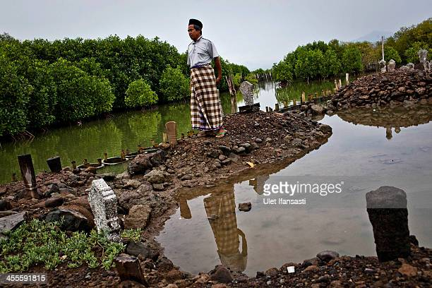 Ahmad Fauzan stands at a public cemetery mostly submerged by rising sea levels at Bedono village on December 12 2013 in Demak Central Java Indonesia...