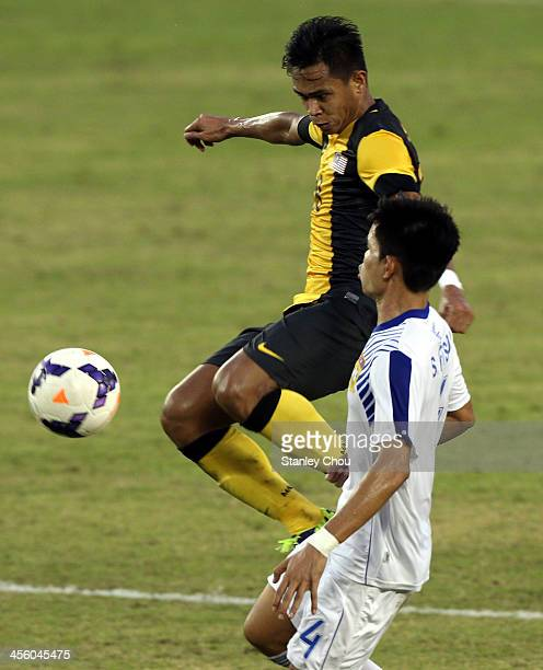 Ahmad Hazwan Bakti of Malaysia scores against Laos as Kedsada Khousamnan of Laos looks on during the Men's Football Competition during the 2013 SEA...