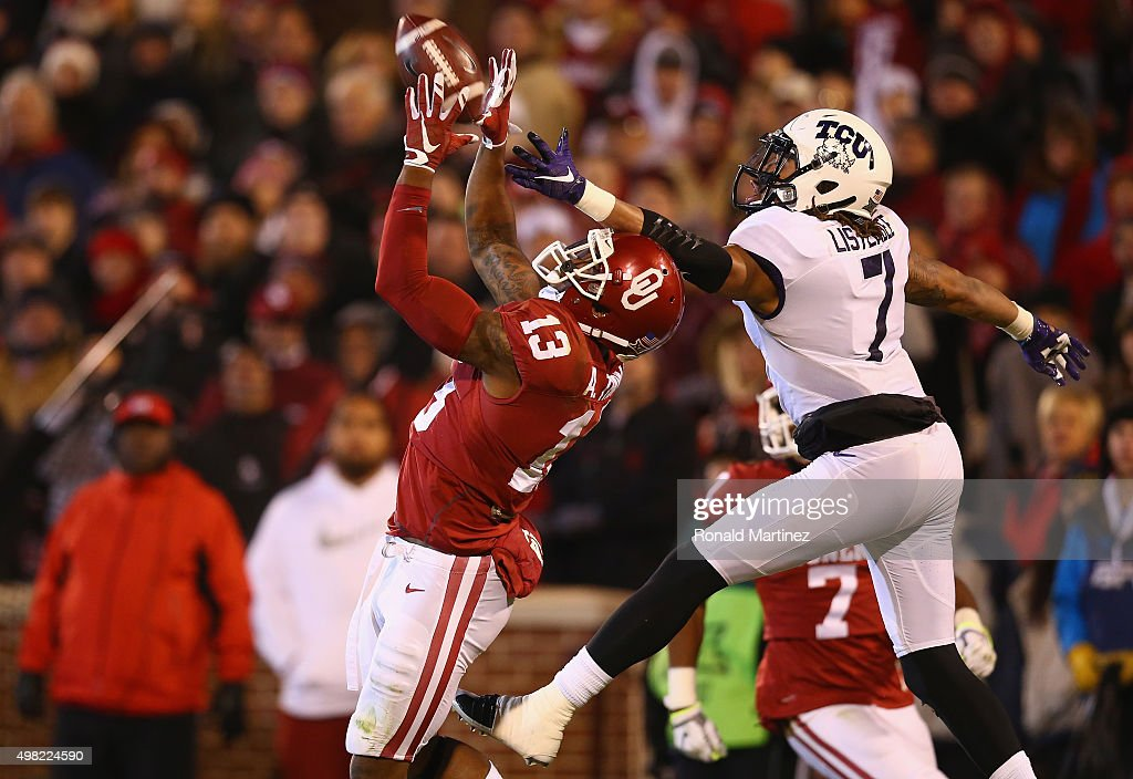 Ahmad Thomas #13 of the Oklahoma Sooners makes a interception against Kolby Listenbee #7 of the TCU Horned Frogs in the third quarter at Gaylord Family Oklahoma Memorial Stadium on November 21, 2015 in Norman, Oklahoma.