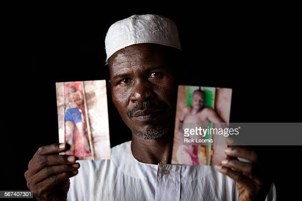 REPUBLIC SATURDAY MARCH 18 2014 Ahmat Moussa holds pictures of his brothers Mahamat Nourene left and Saleh Ahmat who were killed when they tried to...
