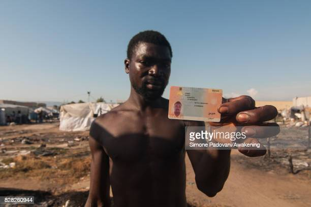 Ahmed Alheji a migrant from Nigeria who has lived in the Rosarno ghetto since 2012 shows his temporary visa on August 9 2017 in Reggio Calabria Italy...