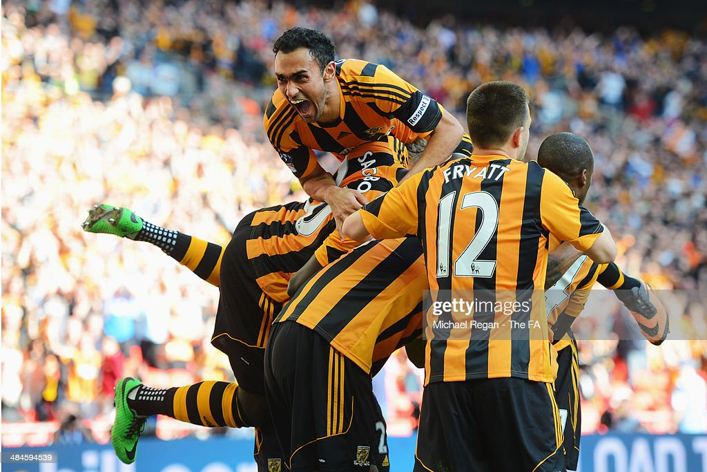 Ahmed Elmohamady (C) and Yannick Sagbo (L) of Hull City jump on top of their team-mate Tom Huddleston after he scored their third goal during the FA Cup Semi-Final match between Hull City and Sheffield United at Wembley Stadium on April 13, 2014 in London, England.