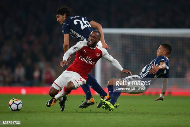 Ahmed Hegazy and Kieran Gibbs of West Bromwich Albion tackle Alexandre Lacazette of Arsenal during the Premier League match between Arsenal and West...