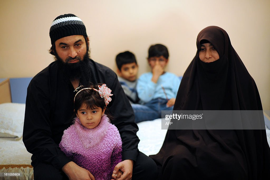 Ahmed Moussa and his wife Shasine pose with their three children during an interview with AFP in the Roma neighborhood in Pazardzhik on February 2, 2013. Ahmed Moussa is accused, along with 12 other Muslim clerics, of 'dissemination of anti-democratic ideology, by the spread of Salafi ideology branch of Islam to impose a state of the caliphate.' SERGUEVA