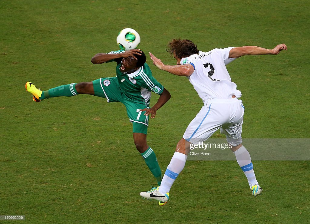 Ahmed Musa of Nigeria tangles with <a gi-track='captionPersonalityLinkClicked' href=/galleries/search?phrase=Diego+Lugano&family=editorial&specificpeople=274735 ng-click='$event.stopPropagation()'>Diego Lugano</a> of Uruguay during the FIFA Confederations Cup Brazil 2013 Group B match between Nigeria and Uruguay at Estadio Octavio Mangabeira (Arena Fonte Nova Salvador) on June 20, 2013 in Salvador, Brazil.