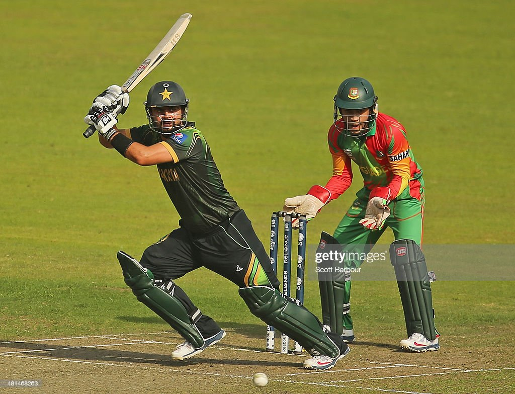 Ahmed Shehzad of Pakistan bats as Mushfiqur Rahim of Bangladesh looks on during the ICC World Twenty20 Bangladesh 2014 match between Pakistan and Bangladesh at Sher-e-Bangla Mirpur Stadium on March 30, 2014 in Dhaka, Bangladesh.
