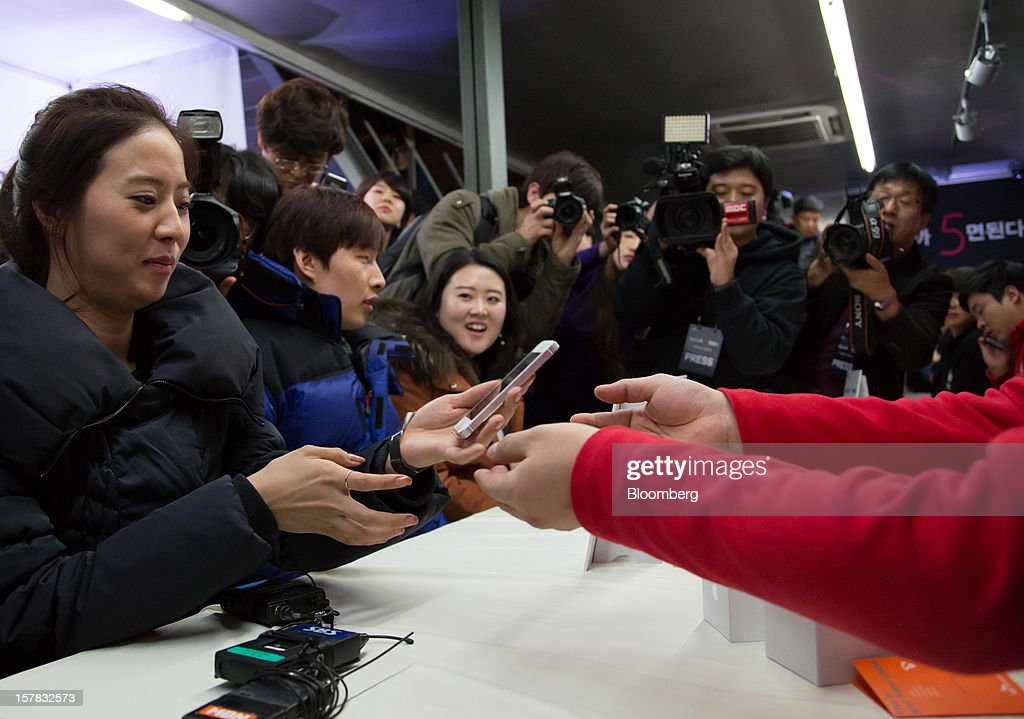 Ahn Hea Jin, 28, the first customer to purchase the Apple Inc. iPhone 5, left, receives the device from an SK Telecom Co. employee during a launch event in Seoul, South Korea, on Friday, Dec. 7, 2012. The iPhone 5 went on sale in South Korea today. Photographer: SeongJoon Cho/Bloomberg via Getty Images