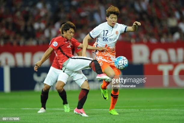 Ahn Hyunbeom of Jeju United FC andTakahiro Sekine of Urawa Red Diamonds compete for the ball during the AFC Champions League Round of 16 match...