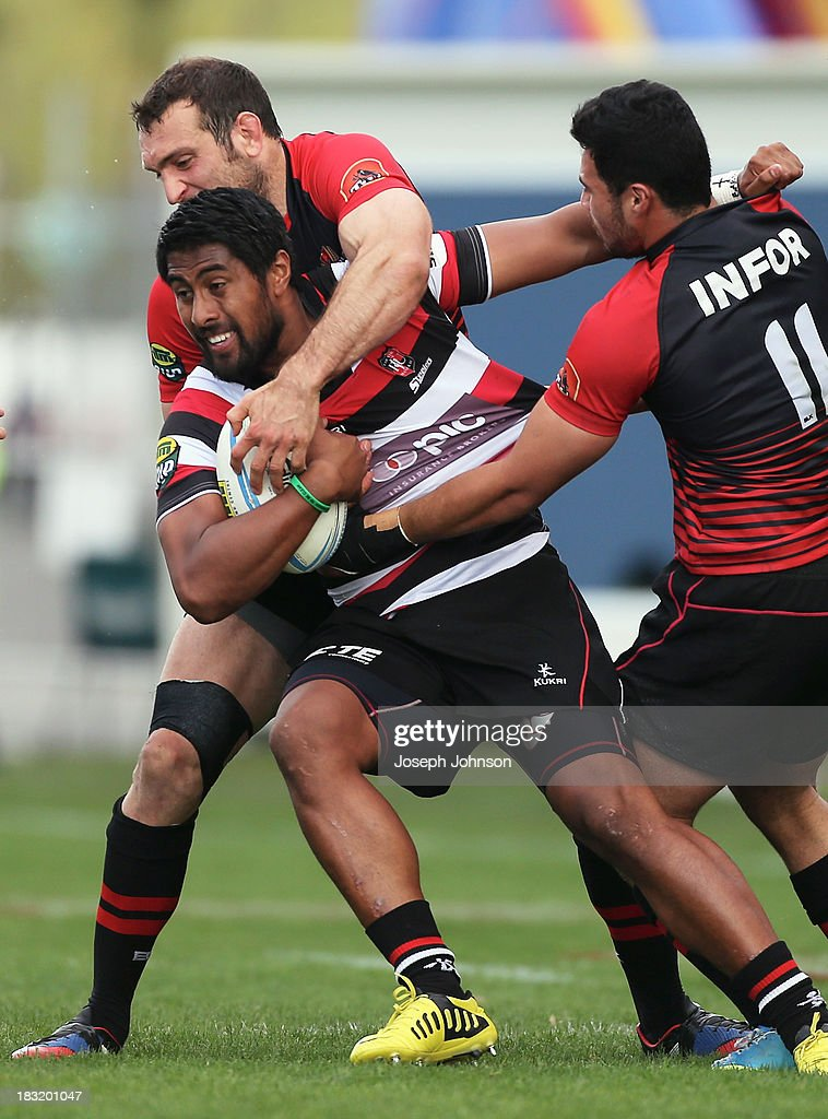 Ahsee Tuala of Counties Manukau with the ball in the tackle of Adam Whitelock and Milford Keresoma of Canterbury during the round eight ITM Cup match between Cantebury and Counties Manukau at AMI Stadium on October 6, 2013 in Christchurch, New Zealand.