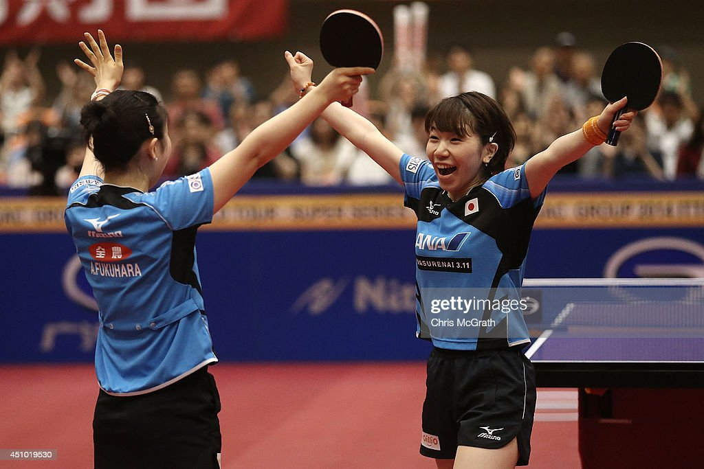 Ai Fukuhara (L) and team mate Misako Wakamiya celebrate victory against Feng Tianwei and Yu Mengyu of Singapore during the Women's Doubles Final on day three of 2014 ITTF World Tour Japan Open at Yokohama Cultural Gymnasium on June 22, 2014 in Yokohama, Japan.