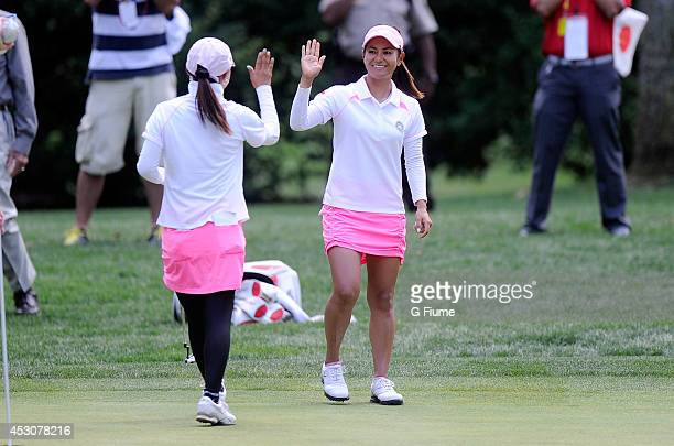 Ai Miyazato of Japan celebrates with teammate Sakura Yokomine after making a putt on the fourth hole during round three of the International Crown at...