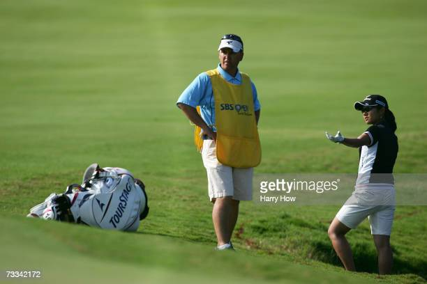 Ai Miyazato of Japan discusses her shot out of a water hazard with her caddie during the first round of the SBS Open the first event of the 2007 LPGA...