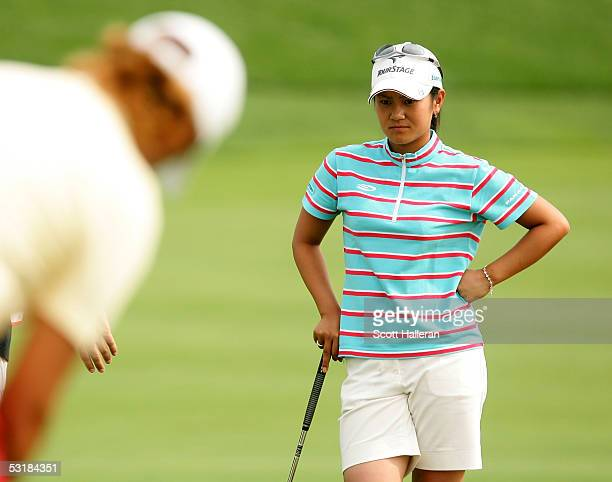 Ai Miyazato of Japan watches Sophie Gustafson of Sweden putt on the eighth green during her match with Gustafson during the third round of the HSBC...