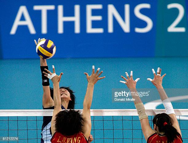 Ai Otomo of Japan spikes the ball against the blocks of Lina Wang and Yanan Liu of China during the women's indoor Volleyball quarterfinal match on...