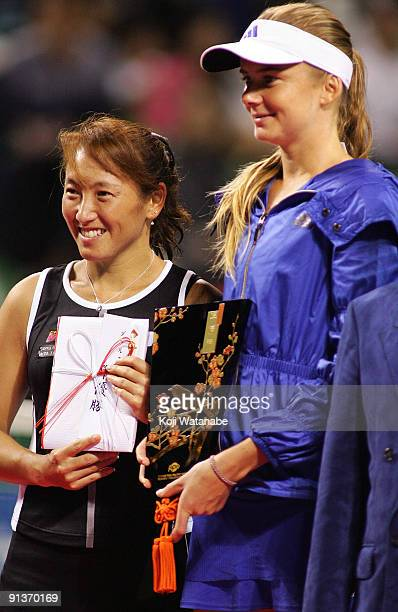 Ai Sugiyama of Japan and Daniela Hantuchova of Slovakia pose with the trophies after playing their doubles final match against Francesca Schiavone of...
