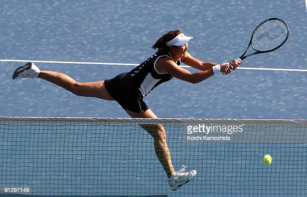 Ai Sugiyama of Japan returns a shot in the women's doubles quarterfinal match with her partner Daniela Hantuchova of Slovakia against Anabel Medina...