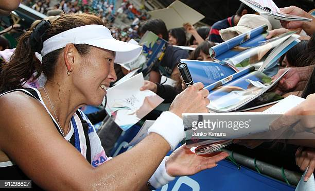 Ai Sugiyama of Japan signs autographs for her fans after playing her doubles match with her partner Daniela Hantuchova of Slovakia against Anabel...