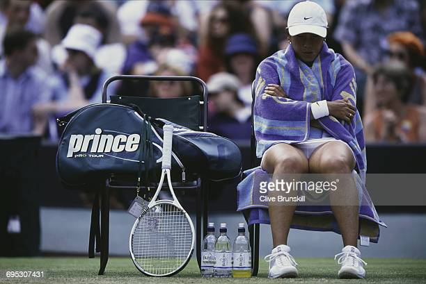 Ai Sugiyama of Japan wraps a towel around herself during the changeover for her Women's Singles third round match Monica Seles at the Wimbledon Lawn...