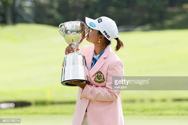 Ai Suzuki of Japan kisses her trophy at the 18th hole after winning the 49th LPGA Championship Konica Minolta Cup 2016 at the Noboribetsu Country...