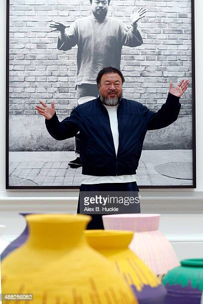 Ai Weiwei stands with his sculpture 'Coloured Vases' as he previews works from His landmark art exhibition at the Royal Academy of Arts on September...