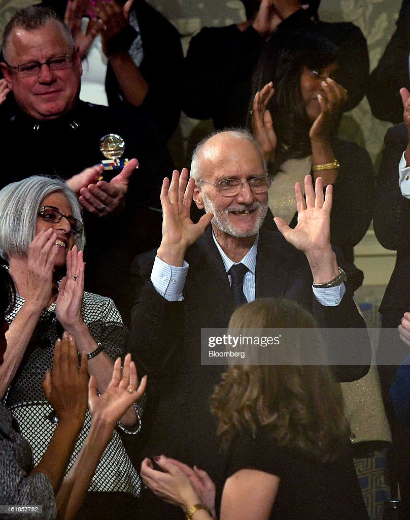 Aid worker Alan Gross, a former Cuban prisoner, center, is applauded as U.S. President Barack Obama, unseen, delivers the State of the Union address to a joint session of Congress in Washington on Tuesday, Jan. 20, 2015. Obama declared the U.S. economy healed and said the nation now must begin work to close the gap between the well-off and the wanting. Photographer: Mandel Ngan/Pool via Bloomberg