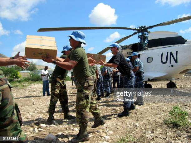 Aid workers receives flood relief supplies in Gonaives Haiti September 21 2004 Relief crews are struggling to get aid to 170000 people affected by...