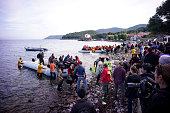 Aid workers wade in the sea to help a migrant boat as it approaches shore after making the crossing from Turkey to the Greek island of Lesbos on...