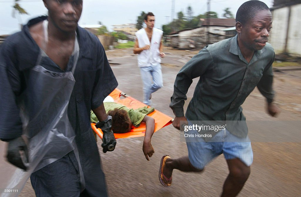 Aid workers with Doctors Without Borders rush an injured girl to a clinic minutes after a shelling attack July 25, 2003 in Monrovia, Liberia. A fresh round of shelling terrorized Monrovia early in the morning, as government forces and rebel troops battled for control of the Liberian capital.