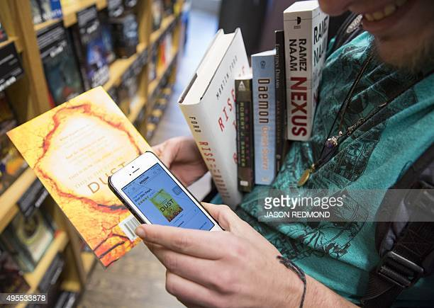 Aidan Devlon of Seattle looks up a book on the Amazon smartphone app as he shops in the new Amazon Books store at University Village in Seattle...