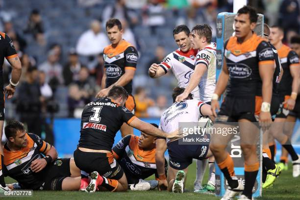 Aidan Guerra Michael Gordon and Connor Watson of the Roosters celebrate Guerra scoring a try during the round 14 NRL match between between the Wests...