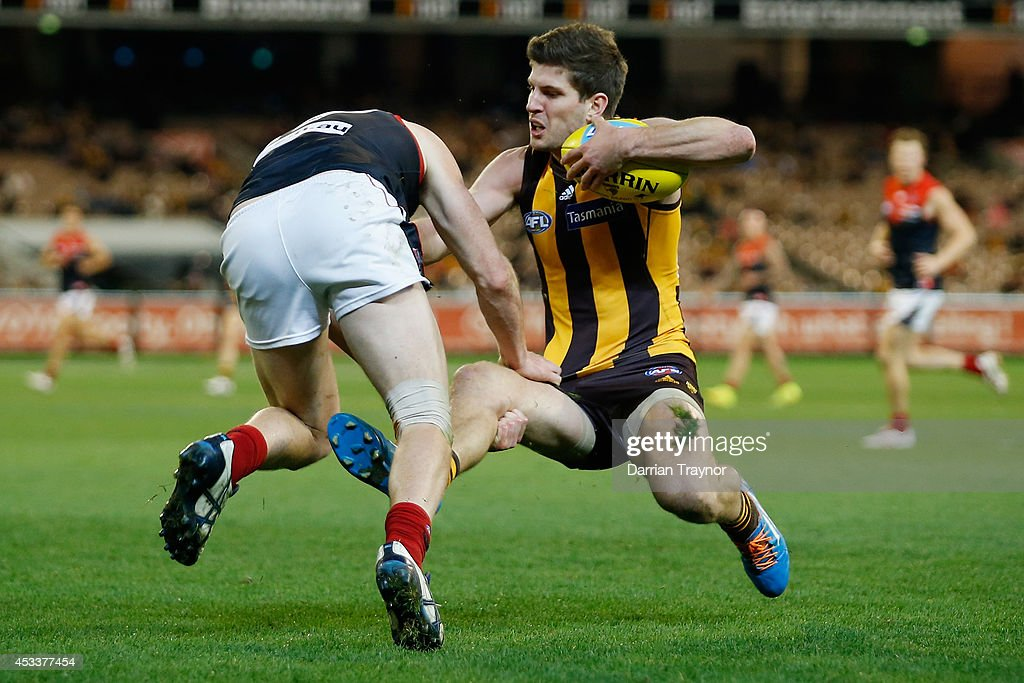 Aidan Riley of the Demons tackles Luke Breust of the Hawks during the round 20 AFL match between the Hawthorn Hawks and the Melbourne Demons at Melbourne Cricket Ground on August 9, 2014 in Melbourne, Australia.