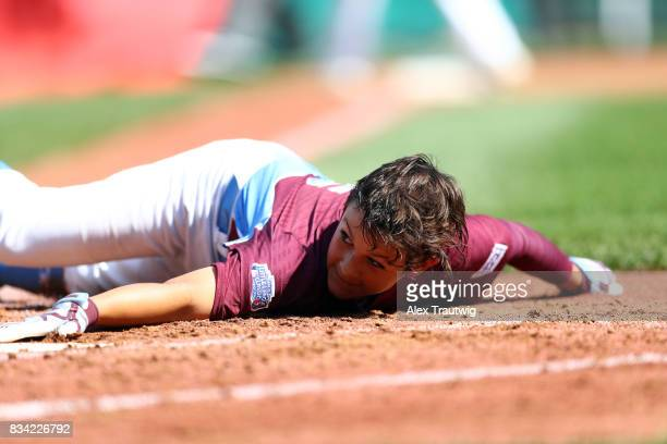 Aidan Rivera of the New England team from Connecticut lays on the ground after being called out at home during Game 2 of the 2017 Little League World...