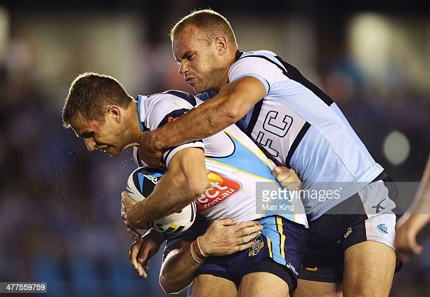 Aidan Sezer of the Titans is tackled by Daniel Holdsworth of the Sharks during the round one NRL match between the Cronulla Sharks and the Gold Coast...