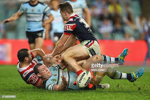 Aiden Guerra and Connor Watson of the Roosters tackle Paul Gallen of the Sharks during the round 19 NRL match between the Sydney Roosters and the...