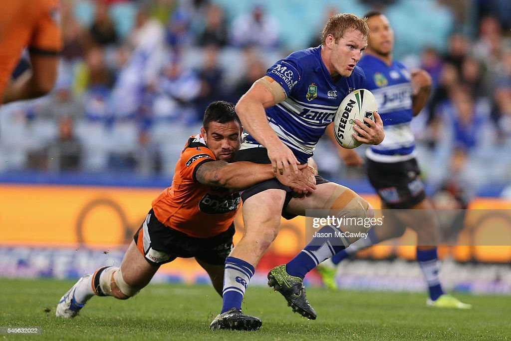 Aiden Tolman of the Bulldogs is tackled by Dene Halatau of the Tigers during the round 18 NRL match between the Canterbury Bulldogs and the Wests Tigers at ANZ Stadium on July 9, 2016 in Sydney, Australia.