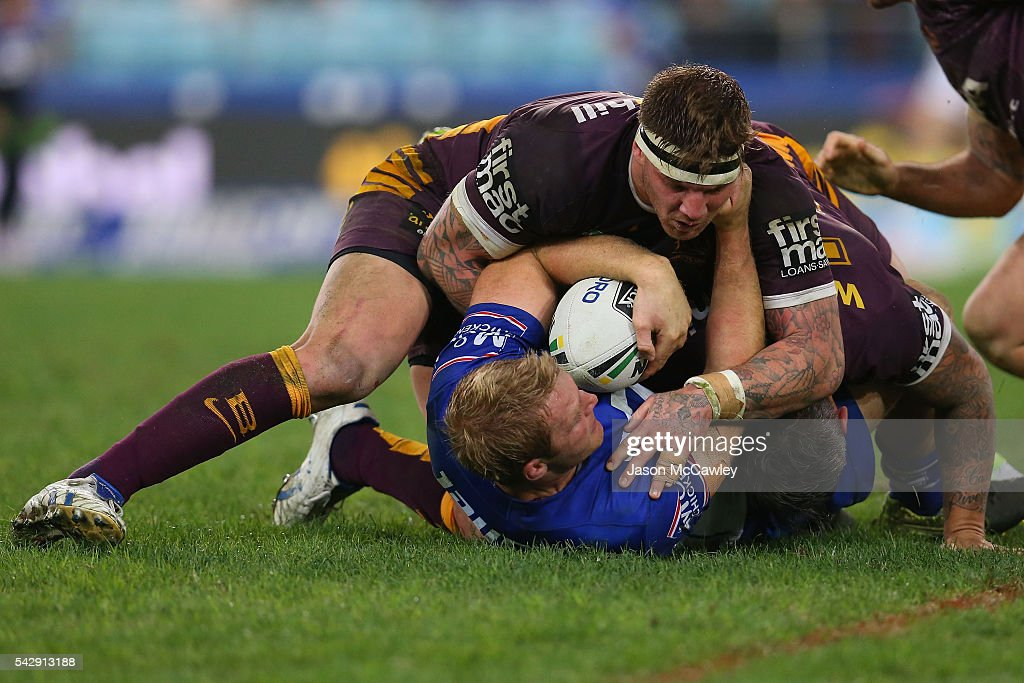 Aiden Tolman of the Bulldogs is tackled by Josh McGuire of the Broncos during the round 16 NRL match between the Canterbury Bulldogs and Brisbane Broncos at ANZ Stadium on June 25, 2016 in Sydney, Australia.