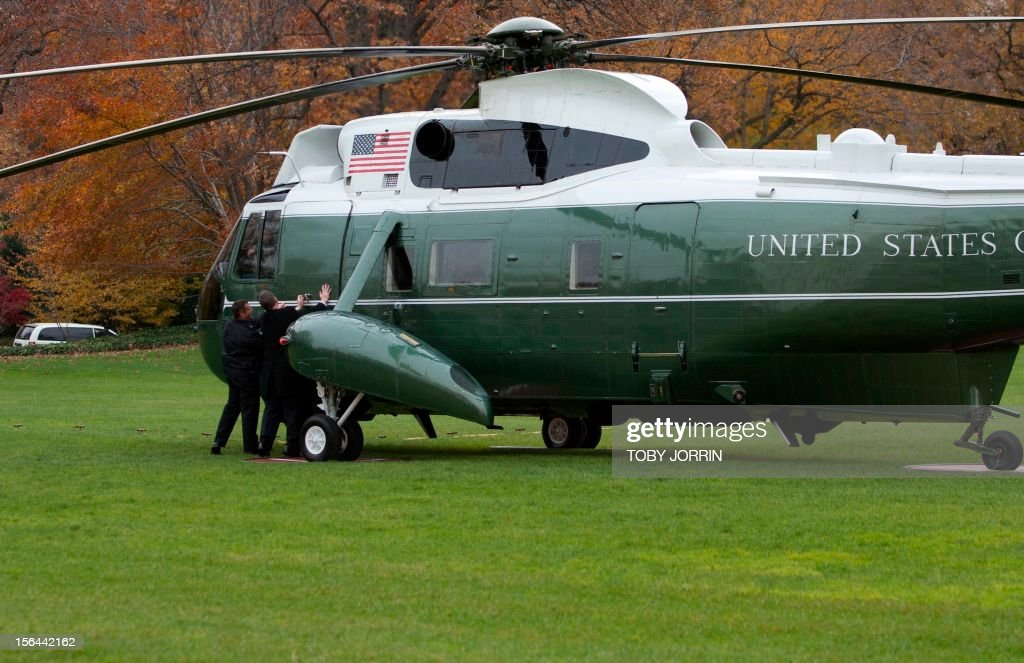 Aides close the door of Marine One as US President Barack Obama departs the White House for a trip to New York City to view storm damage from Sandy on November 15, 2012 in Washington,DC.