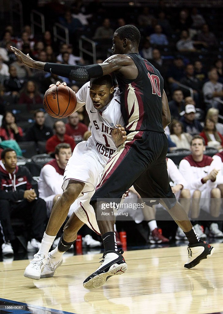 C.J. Aiken #1 of the Saint Joseph's Hawks drives to the basket against Okaro White during the championship game of the Coaches Vs. Cancer Classic at the Barclays Center on November 17, 2012 in the Brooklyn borough of New York City.