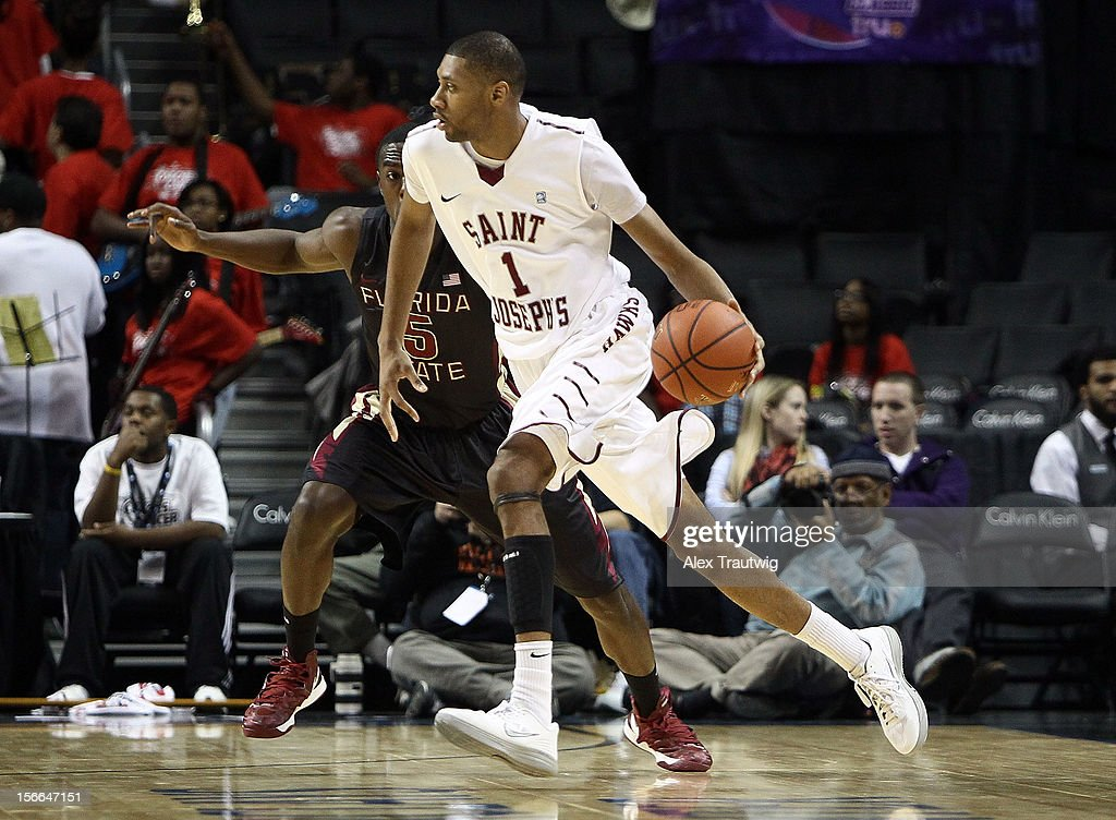 C.J. Aiken #1 of the Saint Joseph's Hawks loooks to pass as Montay Brandon #5 of the Florida State Seminoles defends during the championship game of the Coaches Vs. Cancer Classic at the Barclays Center on November 17, 2012 in the Brooklyn borough of New York City.