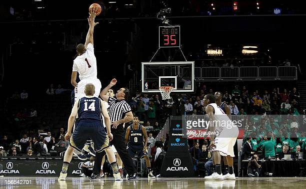 J Aiken of the Saint Joseph's Hawks wins the opening tip against Jack Cooley of the Notre Dame Fighting Irish during their first round game of the...