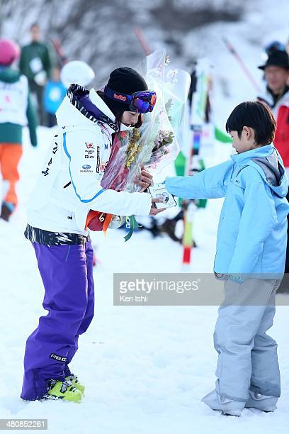 Aiko Uemura of Japan receives a gift from a boy after her final competition in the Women's Finals of the All Japan Freestyle Ski Championships at the...