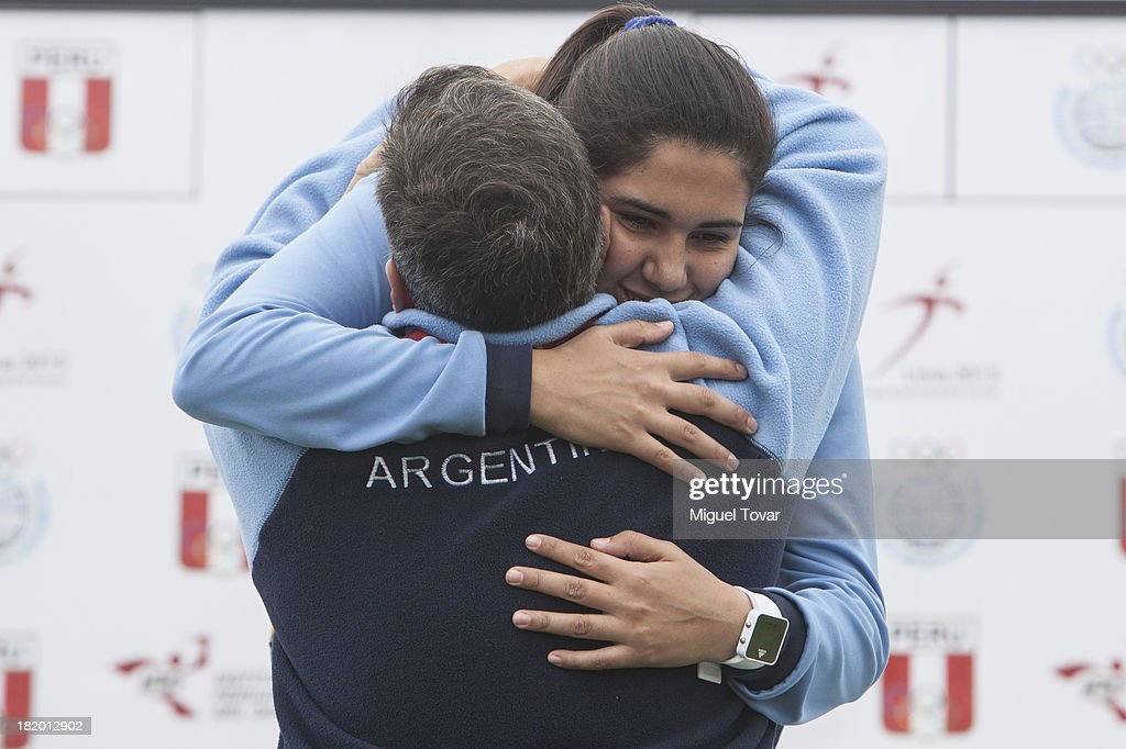 Ailen Armada of Argentina greets her coach in the podium of Women's Discus Throw as part of the I ODESUR South American Youth Games at Estadio Miguel Grau on September 27, 2013 in Lima, Peru.