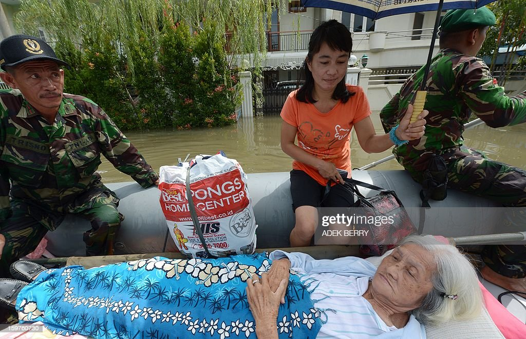 Ailing elderly 87-year-old Loe Giok Tin (bottom) lies in a boat as Indonesian soldiers from the Yon Kes Kostrad evacuate her from a flooded luxury housing complex in Jakarta on January 20, 2013. The death toll from floods in Indonesia's capital Jakarta rose to 15 on January 19 after rescuers found another four bodies. The floods are the worst to hit the capital since 2007 and forced 18,000 people from their homes.