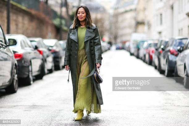 Aimee Song fashion blogger from Song of Style wears a green leather coat a green pleated dress and green shoes outside the Valentino show during...